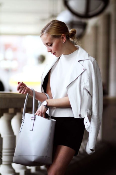 Mujer elegante con peinado de chongo bajo, blusa, bolso y chaqueta de cuero blanco