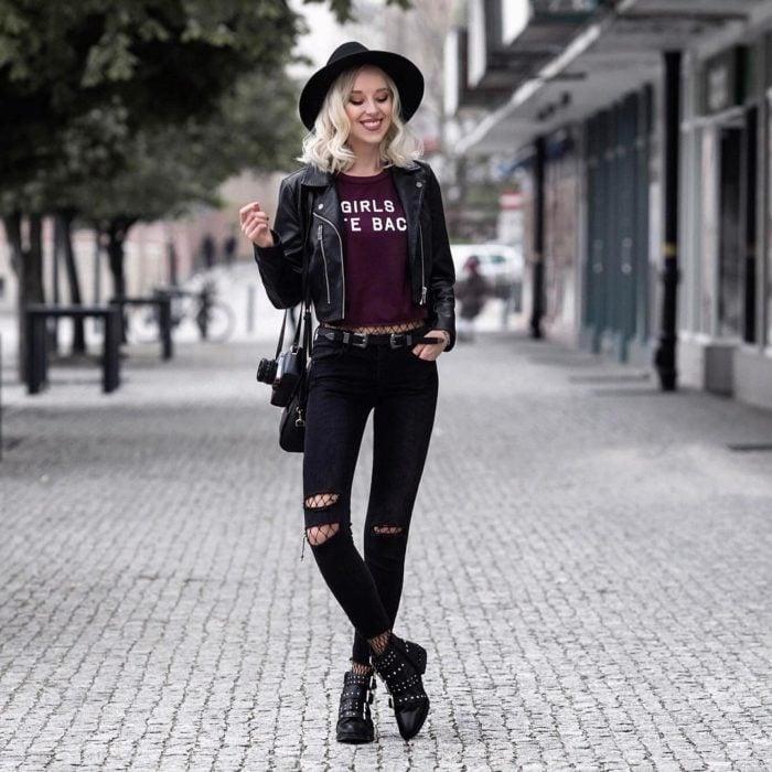 Chica rubia posando para foto en la calle, con sombrero boho, chamarra de cuero, blusa básica guinda, jeans entubados y botas con estoperoles; con cámara analógica