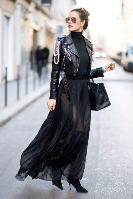 Mujer elegante con chaqueta de cuero con cadenas, falda de tul transparente y bolsa negra