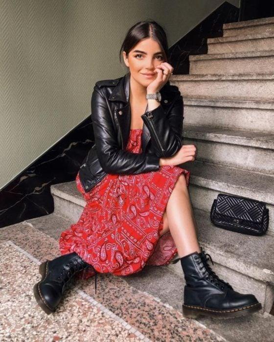 Chica sentada en las escaleras con vestido de tela de paliacate rojo, chamarra de cuero negro, botas Dr. Martens y reloj de mano