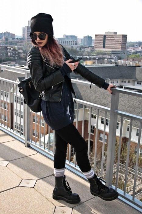 Chica ruda con gorro para el frío, lentes de sol, leggins, botas Dr. Martens con calcetas rayadas y chamarra negra de cuero