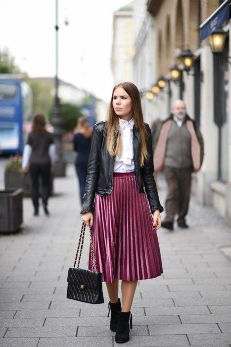 Chica de cabello castaño y lacio, posando para foto en la calle, con falda larga tableada de color rosa, chamarra de cuero negra y bolsa con cadenas