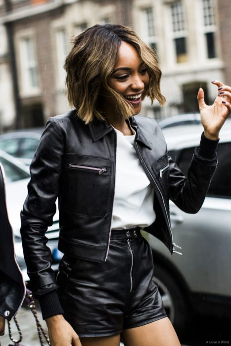 Chica morena de cabello con corte bob arriba de los hombros, con chaqueta y short de cuero negro