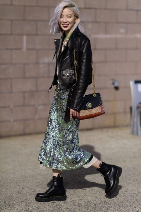 Chica coreana de cabello corto teñido de lila, con chamarra de cuero negro, vestido largo de lentejuelas verdes y botas Dr. Martens