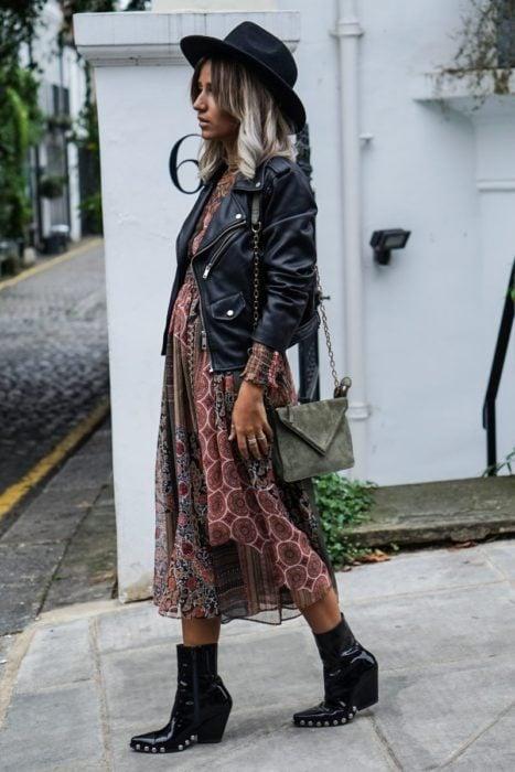 Chica con estilo boho, sombrero, chaqueta de cuero negro, vestido hippie y botas de tacón grueso con estoperoles
