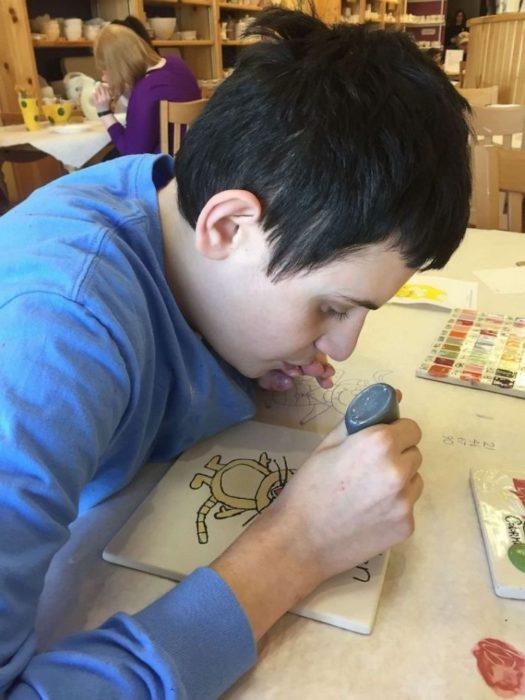 Daniel Dublin, chico con autismo, dibujando con pintura plástica