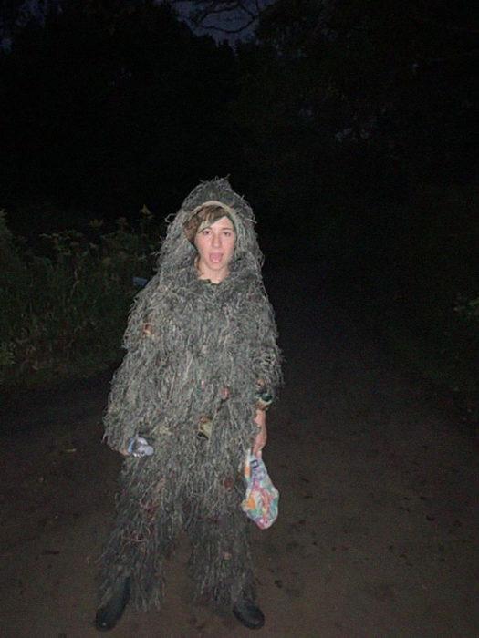 Chica caminando por un sendero disfrazada de arbusto