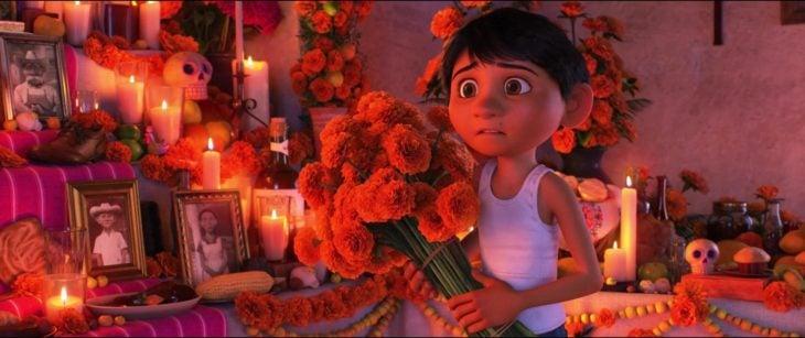 Escena de Coco, Pixar, Miguel dejando flores en el altar de muertos