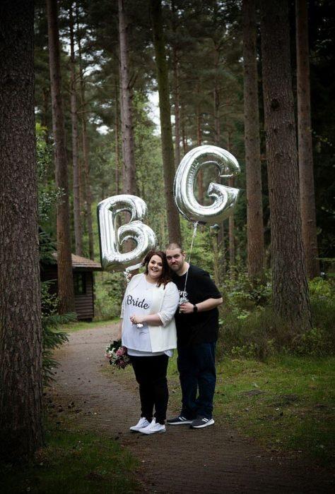 Rebecca y Glen Maxwell en un bosque con una cabaña de fondo y un globo plateado cada quien con la inicial de su nombre