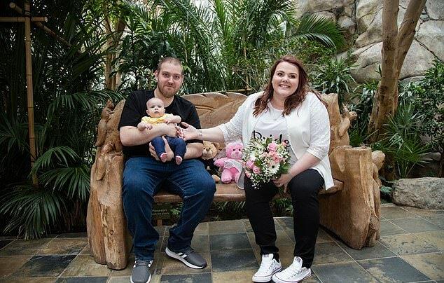 Rebecca y Glen Maxwell en una banca de madera con su hija