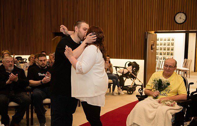 Rebecca y Glen Maxwell se dan un beso en el lugar de la ceremonia de boda