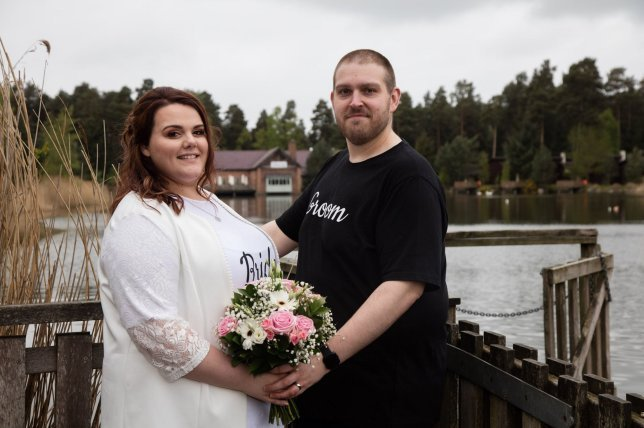 Rebecca y Glen Maxwell posan con el ramo de novia a la orilla de un lago, al fondo se ve un bosque y una cabaña de madera