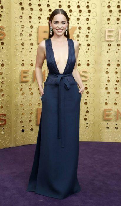 Emilia Clarke usando un vestido de color azul marino con escote mientras posa en la alfombra roja de los premios Emmy 2019