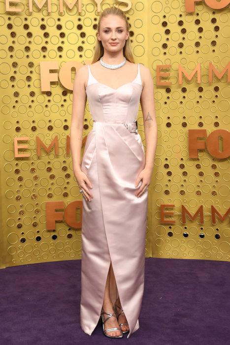 Sophie Turner usando un vestido de color rosa pastel mientras posa en la alfombra roja de los premios Emy 2019