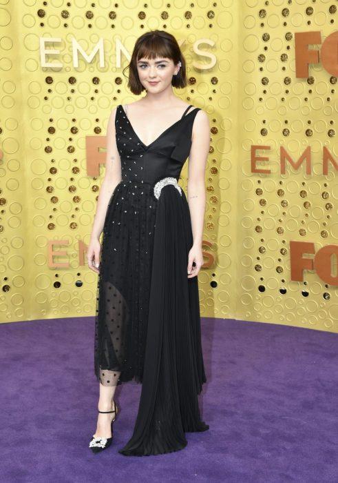 Maisie Williamsusando un vestido de color negro con aplicaciones de brillos mientras posa en la alfombra roja de los premios Emmys 2019