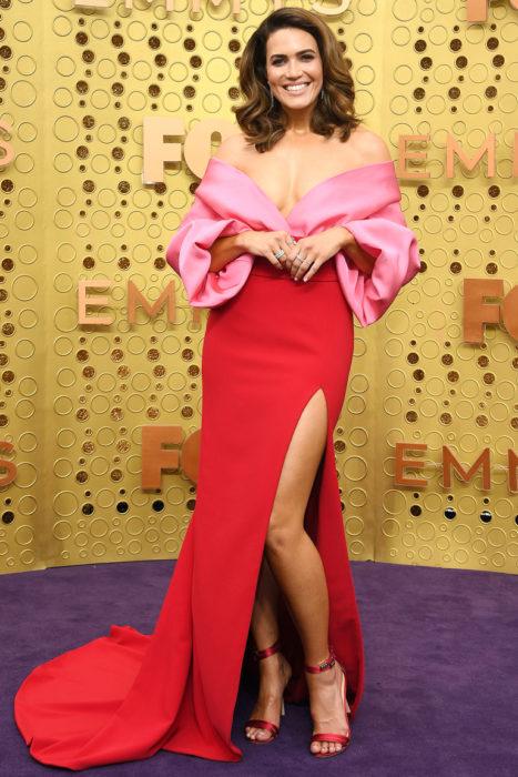 Mandy Mooreusando un vestido de color rosa y rojo mientras posa para la alfombra roja de los premios emmy 2019