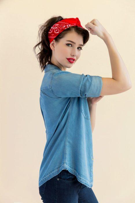 Chica usando una camisa de mezclilla, pantalón azul y pañoleta de color rojo en la cabeza