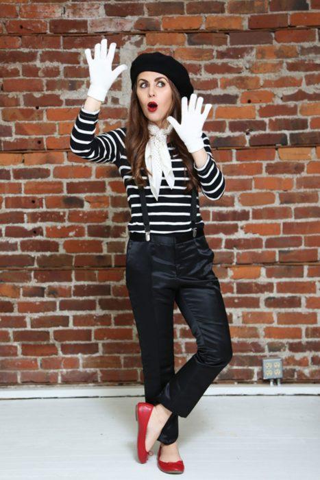 Chica vestida con un pantalón negro, camisa a rayas y guantes de color blanco