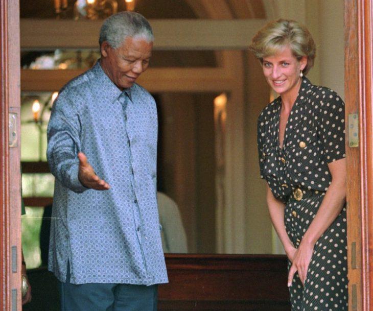 Diana de Gales con Nelson Mandela quien hace una señal de cederle el paso