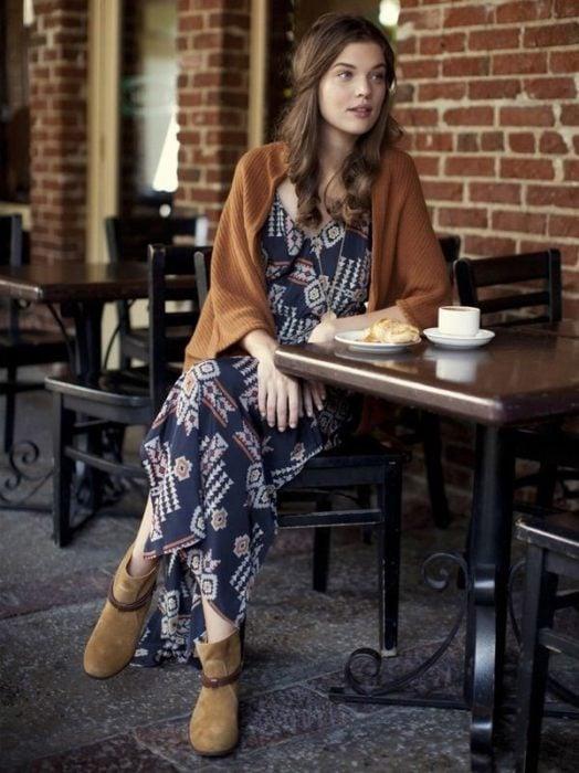 Ropa estilo boho o hippie chic; chica sentada en una mesa de un café con maxivestido holgado azul, con chal y botines