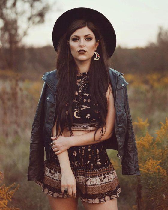 Ropa estilo boho o hippie chic gótica; chica de cabello largo, con aretes de luna, crop top y short de tela de paliacate, chamarra de cuero negro
