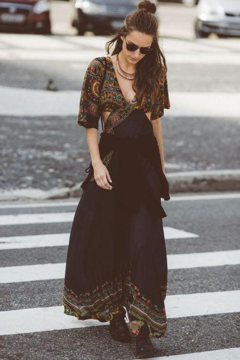 Ropa estilo boho o hippie chic; chica caminando en cruce peatonal con maxivestido negro