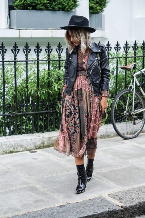 Ropa estilo boho o hippie chic; chica caminando en la calle, con vestido fresco de tela de paliacate, sombrero, chaqueta de piel negra y botines de charol