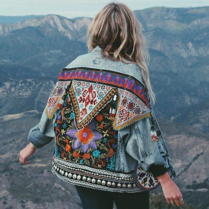Ropa estilo boho o hippie chic; mujer en las montañas con chamarra de mezclilla con tejido indígena