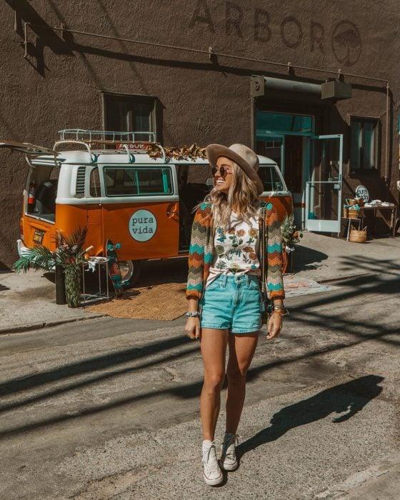 Ropa estilo boho o hippie chic; chica frente a una van, sonriendo con sombrero, lentes de sol, playera con estampado de flores, abrigo tejido de colores, short de mezclilla y tenis blancos converse