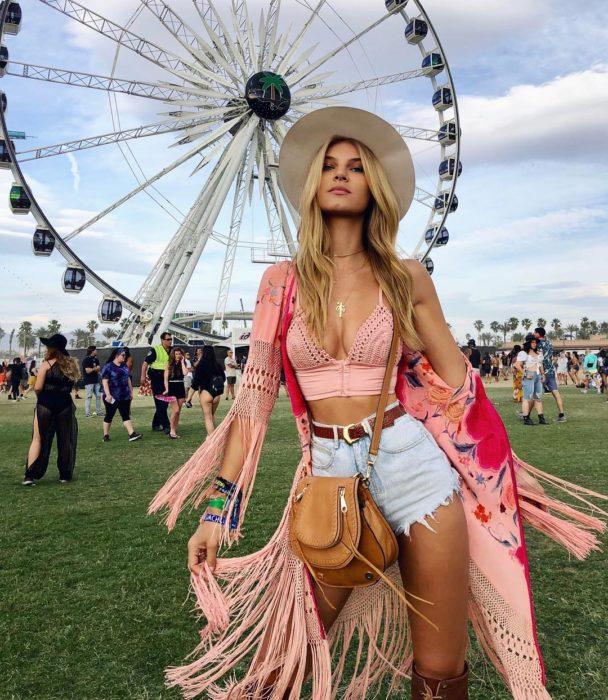 Ropa estilo boho o hippie chic; mujer frente a una rueda de la fortuna en festival, con sombrero beige, crop top rosa, chalina con flecos, short de mezclilla