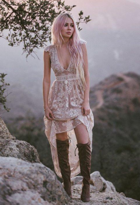 Ropa estilo boho o hippie chic; mujer en la montaña, de cabello largo y rosa, con vestido de encaje y botas largas cafés