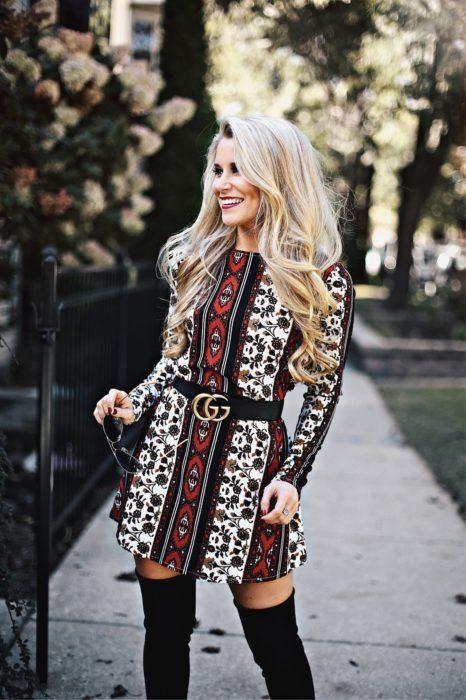 Ropa estilo boho o hippie chic; mujer en la calle, con cabello largo rubio y platinado, con vestido con patrones y cinto