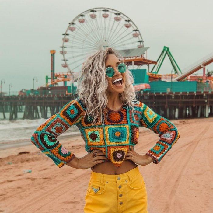 Ropa estilo boho o hippie chic; chica de cabello rubio platinado chino hasta los hombros, con crop top tejido, con jean amarillo, sonriendo con las manos en la cintura frente a un parque de diversiones con rueda de la fortuna