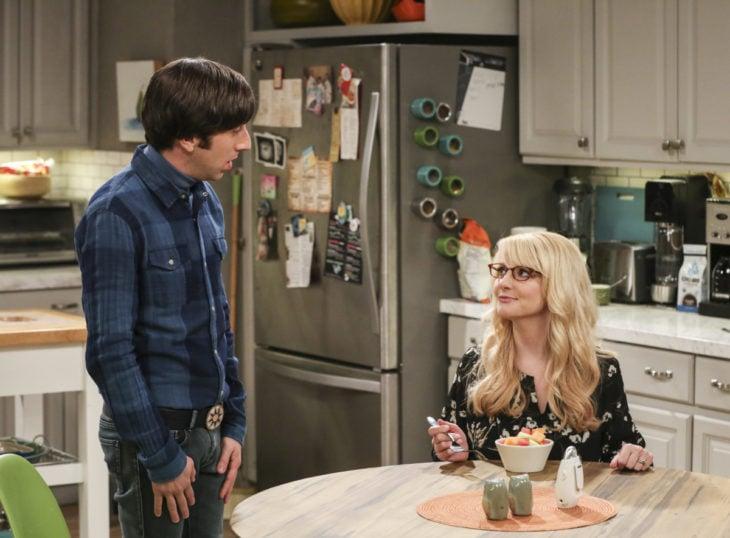 una pareja en la cocina, ella está sentada frente a la mesa y él parado mientras le habla