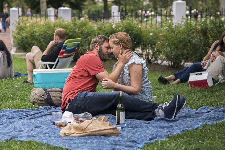 una pareja haciendo un picnic en un parque sentados sobre una manta azul, se tocan la cara