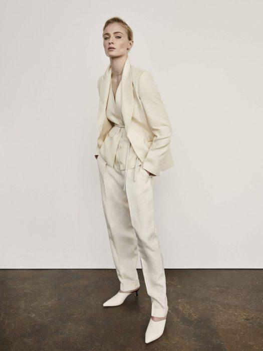Famosas con traje; Sophie Turner con saco y pantalón de gala color blanco marfil, y peinado de cola de caballo sencillo