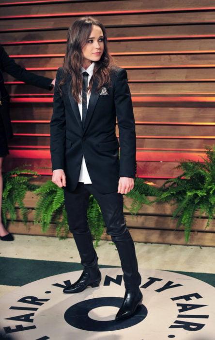 Famosas con traje; Ellen Page con saco y pantalón negro con camisa blanca y corbata, cabello largo y suelto