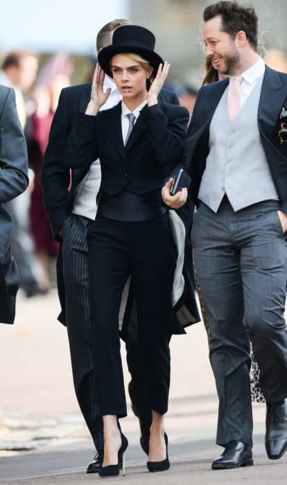 Famosas con traje; Cara Delevingne con saco y pantalón de gala negros con sombrero de copa, tacones y corbata