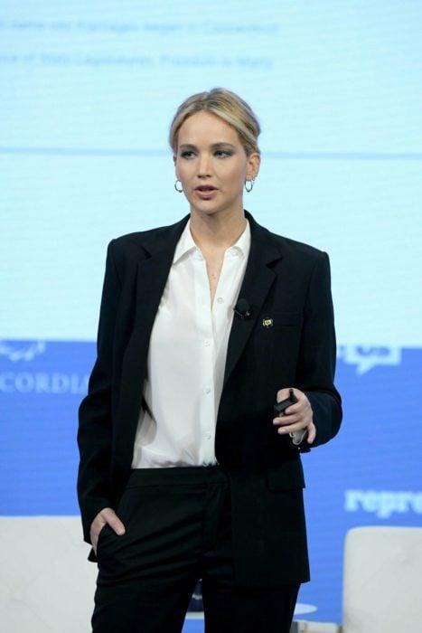 Famosas con traje; Jennifer Lawrence con saco y pantalón de vestir negro con camisa blanca, peinado de cola de caballo sencillo