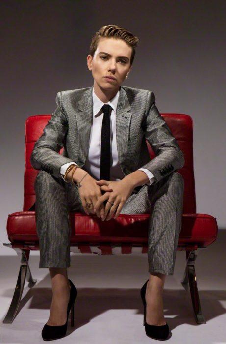 Famosas con traje; Scarlett Johansson con cabello corto pixie, con saco y pantalón de vestir gris briññante, con camisa blanca y corbata negra, sentada en un sillón rojo
