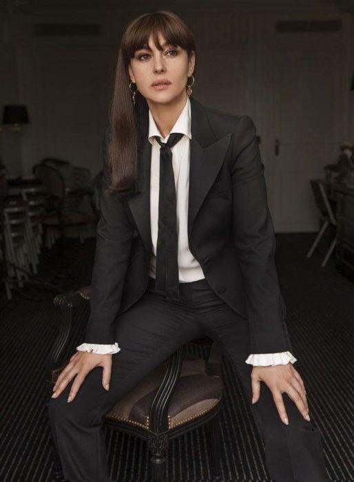 Famosas con traje; Monica Bellucci con saco y pantalón de vestir negro, con camisa blanca y corbata negra, cabello largo, lacio y suelto