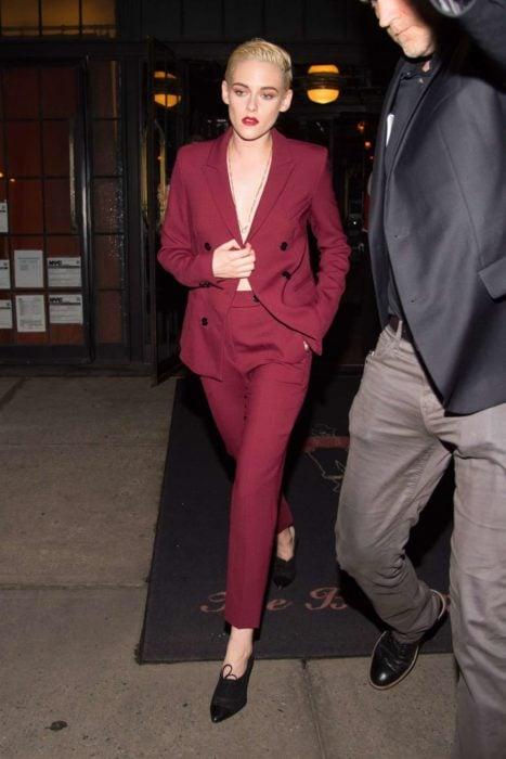 Famosas con traje; Kristen Stewart con cabello corto, pixie, rubio, vestida con saco y pantalón de vestir color rojo vino