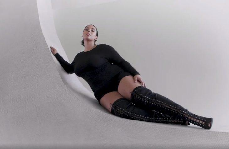 una modelo de talla grande recostada en una pared con botas altas arriba de la rodilla