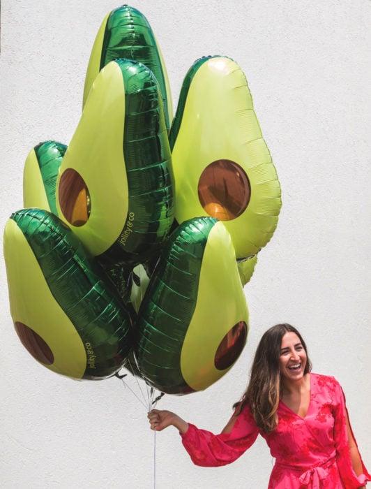 Fiesta temática de aguacate; chica sosteniendo globos