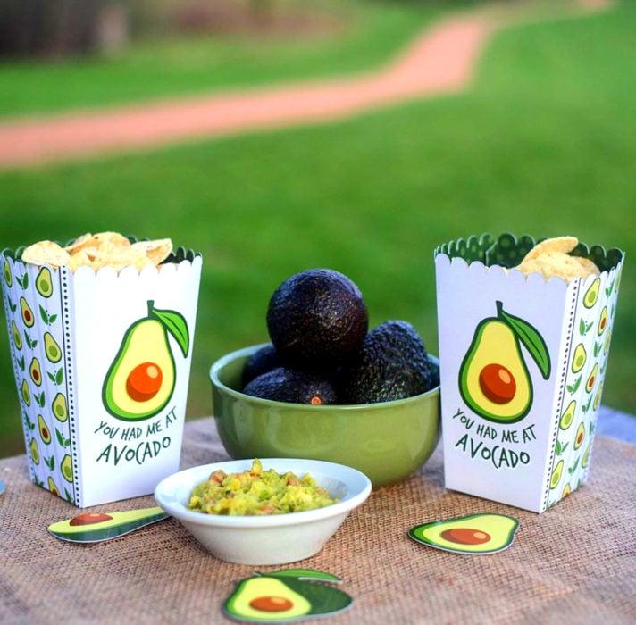 Fiesta temática de aguacate; mesa de aperitivos con guacamole y caja con papas