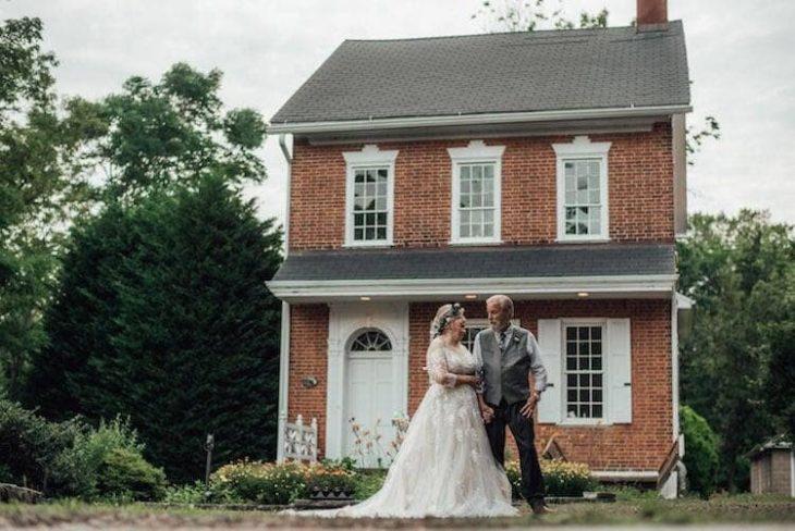 George y Ginger Brown posando fuera de una casa vieja, usando ropa de bodas