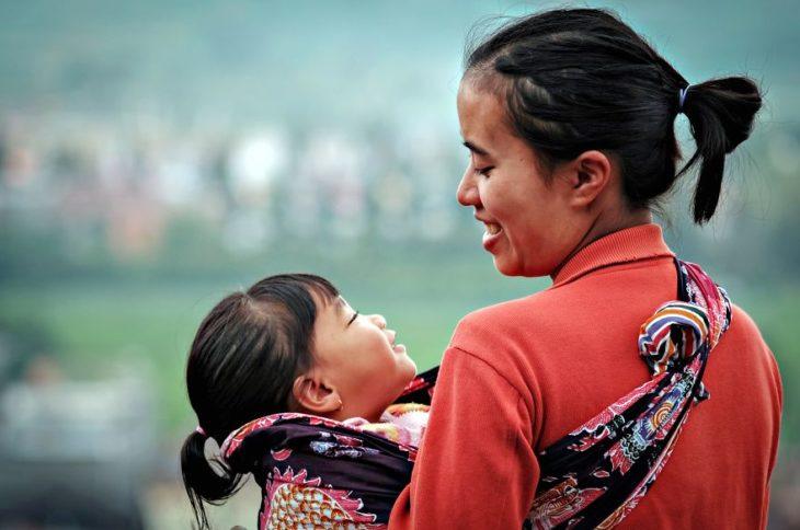 Madre viendo a su hija mientras la sostiene en el regaso