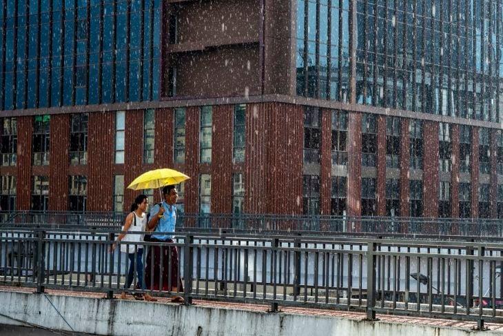 Pareja de novios caminando bajo la lluvia y cubriéndose con una sombrilla