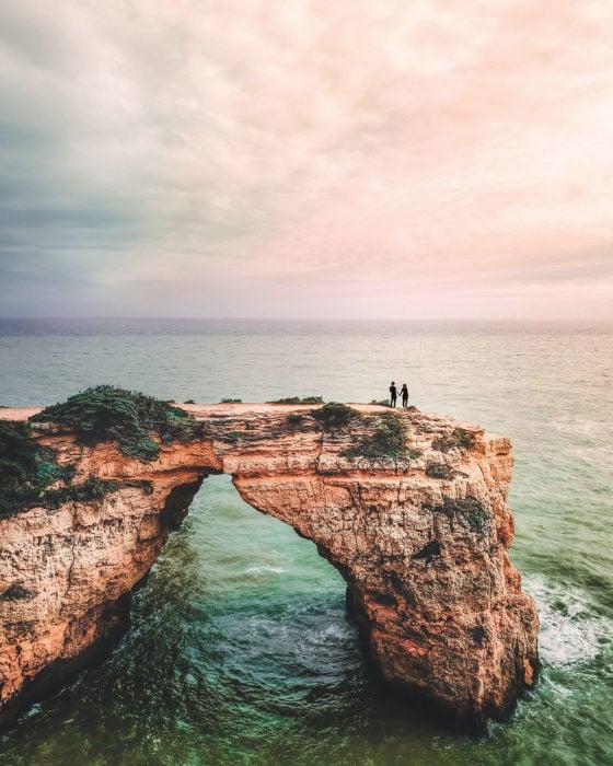 Pareja de novios parados en una roca y dándose un beso