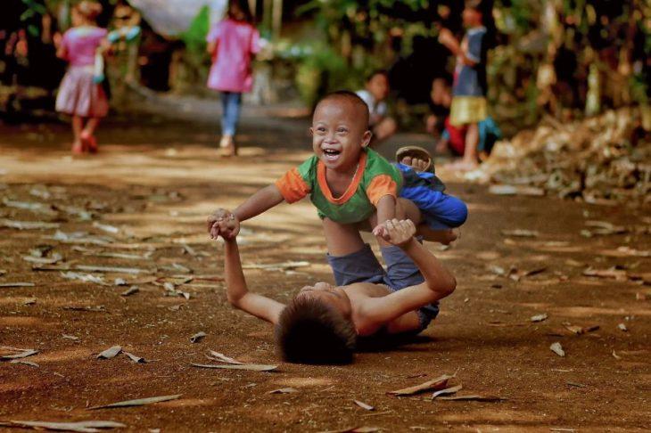 Niños jugando mientras están en medio de la tierra